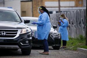 27日、米南部ルイジアナ州ニューオーリンズで、乗用車の運転手と話す医療関係者(ロイター=共同)