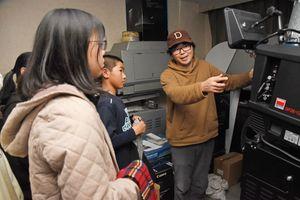 シアター・シエマの芳賀代表の説明を受け、興味深げに映写機を見つめる児童たち=佐賀市のシアター・シエマ