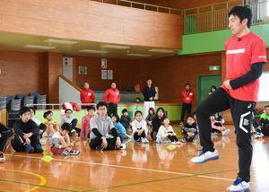 参加者に走り方を指導する朝原宣治さん=佐賀市の市立体育館