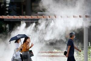 各地で厳しい残暑となった秋分の日、東京・銀座では日傘を差したり、設置されたミストシャワーの近くを歩いたりして、暑さをしのぐ人たちの姿が見られた=23日午後