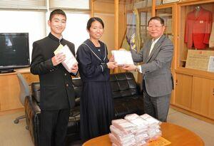 マスクを手渡す吉野ヶ里町の伊東健吾町長(右)と受け取る東脊振中の生徒=吉野ヶ里町の同校