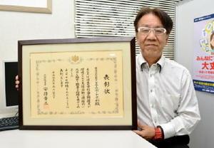 内閣総理大臣賞の表彰状を手にする陣内誠理事長=佐賀市神野東のITサポートさが