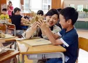 児童と話し合いながら焼き物作りを手伝う有田工業高生=有田中部小