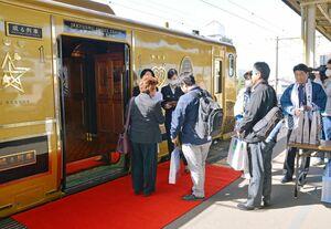 佐賀特産のお土産を受け取り「或る列車」に乗り込む乗客ら=JR佐賀駅