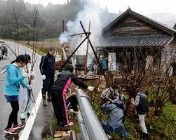 のり面に生えたコウゾの枝を収穫する参加者ら=嬉野市塩田町