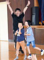 ゲームを楽しむ児童らと、人形劇団「デフ・パペットシアター・ひとみ」の善岡修代表(左奥)=佐賀市の県立ろう学校