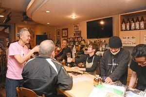 ウシャコダのライブ後、乾杯してたたえる一力千恵さん(中央)。稲葉浩さん(右から2人目)はライブ運営を支えてきた=唐津市二タ子