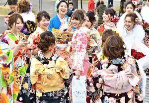 成人式の会場で久しぶりに再会する友人たちに笑顔を見せる新成人たち=2019年1月、佐賀市文化会館