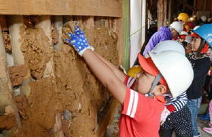 泥団子を手に、壁に塗り付けていく児童たち=鹿島市の幸姫酒造
