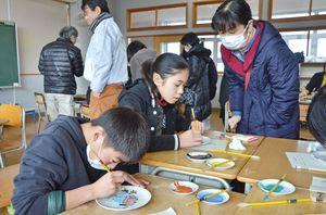 白磁の皿に思い思いの図柄を描き、筆と絵の具で着色していく子どもたち=佐賀市の開成小