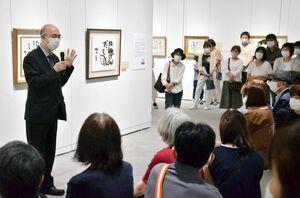 父である相田みつをが作品に込めた思いやエピソードを紹介する相田一人館長=佐賀市の佐賀県立美術館