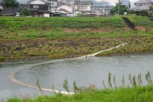 塩田川に流出した重油を回収するため設置された吸着マット=26日、嬉野市塩田町の塩田橋付近
