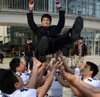 佐賀大学に合格し、アメフット部員に胴上げで祝福される受験生=佐賀市の佐賀大本庄キャンパス