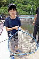 ニジマス釣りの強い引きを楽しんでいた子ども=唐津市厳木町平之のフィッシングパークひらの