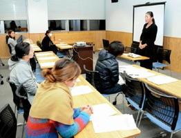 秋山理事長から新保育園の説明を聞く参加者たち=佐賀市白山の佐賀商工ビル