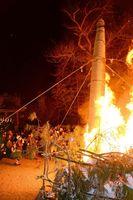 積み上げられた正月飾りを燃やす巨大なたいまつを支える消防団員=唐津市十人町の唐津天満宮