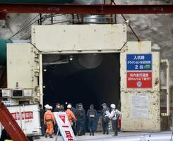 事故があった関西電力高浜原発1、2号機敷地内のトンネルで実況見分をする警察官ら=20日午前、福井県高浜町