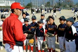 迎祐一郎会長から守備の指導を受ける子どもたち=神埼市の神埼中央公園グラウンド