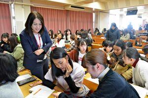 質問を考える生徒に声を掛ける田町幸子さん=佐賀市本庄町の佐賀女子短大