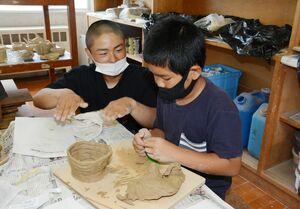 有田工生から教わり、使いたい焼き物を成形する児童たち=有田町の大山小