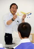 模型を使って飛行機の進化の歴史や今後について語る麻生茂教授=白石町の福富ゆうあい館