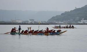 太鼓やドラが打ち鳴らされ、懸命にオールをこぐ参加者=唐津市西の浜