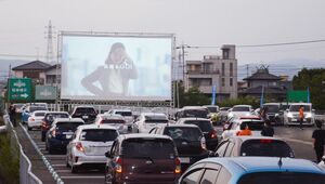 大型スクリーンの前に並んだ車。車の中から映画を楽しんだ=佐賀市のモラージュ佐賀