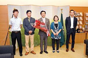 山口祥義知事(中央)にバラを手渡した石川栄治さん(左から2人目)と奈津子さん(右から2人目)夫妻=県庁