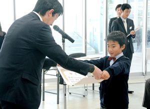 笑顔で賞状を受け取る受賞者=佐賀市の佐賀大学美術館