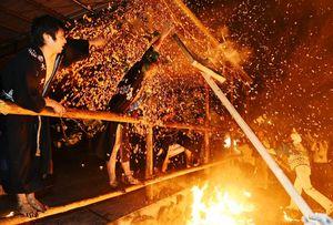 五穀豊穣を祈願し、火の粉が飛び交う中で激しい攻防を繰り広げる男衆=伊万里市二里町大里の神之原八幡