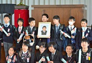 駿君の遺影と一緒に記念写真に収まる卒業生=佐賀市の西与賀小