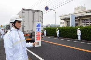 仮庁舎前でドライバーに「追突注意」の札を掲げる署員=大町町の白石署仮庁舎前