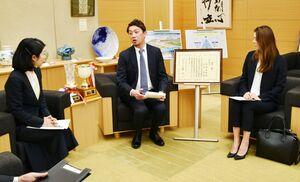 小林副知事(左)に大臣賞受賞を報告する宮崎陽輔さん(中央)と妻の舞さん=佐賀県庁