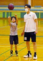 参加者のスローを見守る佐賀バルーナーズの水町亮介アカデミーコーチ(右)=佐賀市立体育館