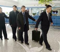 平壌国際空港を出発する北朝鮮オリンピック委員会副委員長のキム・ジョンス第1体育次官(右端)ら=15日(共同)