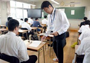 県警のA採用試験で、答案用紙を受け取る受験者たち=佐賀市の佐賀工高