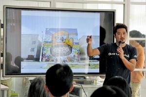 壁画を見せながら、願いを語るミヤザキケンスケさん=佐賀市の県国際交流プラザ
