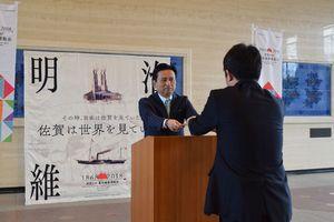 副部長級の県職員に委嘱状を手渡す山口祥義知事(左)=佐賀県庁