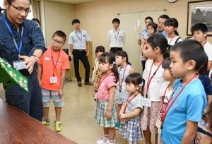 担当者から階級章の説明を受ける子どもたち=佐賀市の県警本部
