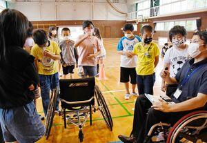 車いすを興味深く見つめる北波多小の5年生。右は講師の松本幸貴さん=唐津市の同校
