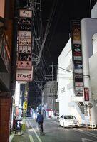 休業や時短営業の要請に応じ、看板の明かりが消えた商業ビル=佐賀市の愛敬通り(昨年4月22日撮影)