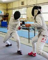 フェンシング女子個人フルーレ決勝 積極果敢に攻撃する佐賀商の岸川莉紗(左)=佐賀市の県フェンシング場