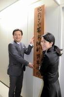 10日付で設置された肥前さが幕末維新博事務局の看板を掛ける山口祥義知事(左)=佐賀県庁