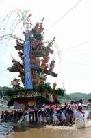 力を合わせ、巨大山笠を勢いよく海から引き上げる地元の男衆=唐津市呼子町の小友漁港