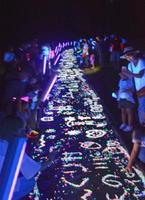 ブラックライトに照らされて浮かび上がった「天の川」を楽しむ来場者=佐賀市三瀬村の三瀬ルベール牧場どんぐり村