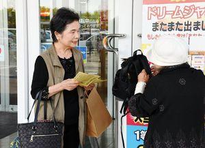 買い物客と対話しながらチラシを配布する市民ボランティア(左)=鳥栖市本鳥栖町のフレスポ鳥栖