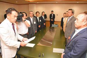 田中秀和議長(手前右)から申し入れ書を受け取った峰達郎市長(左)=唐津市役所