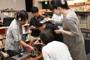 当日の上映会に向け、事前に音声機器の準備をするみないろ会のメンバーたち=佐賀市松原のシアター・シエマ