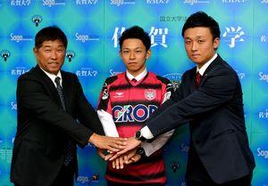 岡山のユニホームに袖を通した松本健太郎(中央)。左は佐賀大の坂元康成監督、右は岡山の西原誉志強化担当=佐賀市の同大本庄キャンパス
