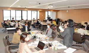 閉会中の活動や選挙活動などグループごとに分かれて情報交換したワークショップ=神埼市役所
